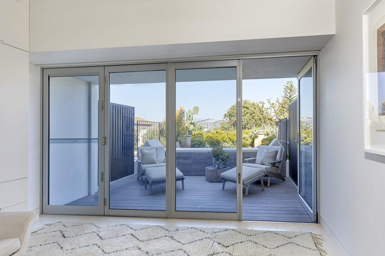Paragon bi-fold door and sashless window in clear anodised finish